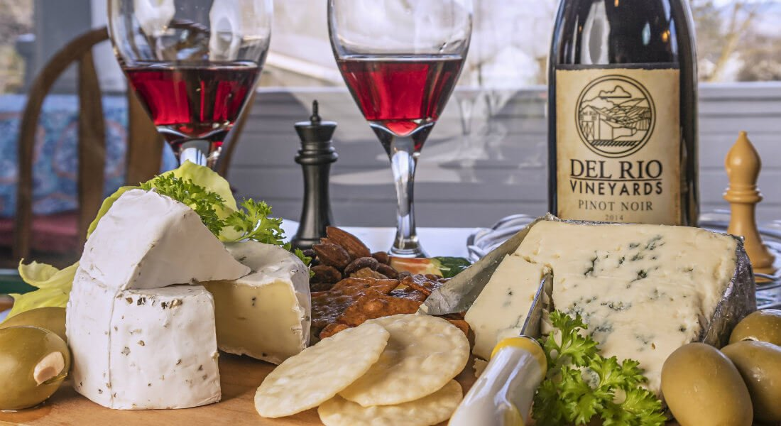 Several sliced gourmet cheeses surrounded by stuffed olives, water chestnut crackers, and two glasses of red wine