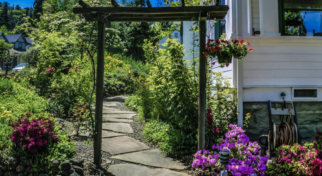 A wooden trellis entrance over a stone path leading back into a garden of green plants