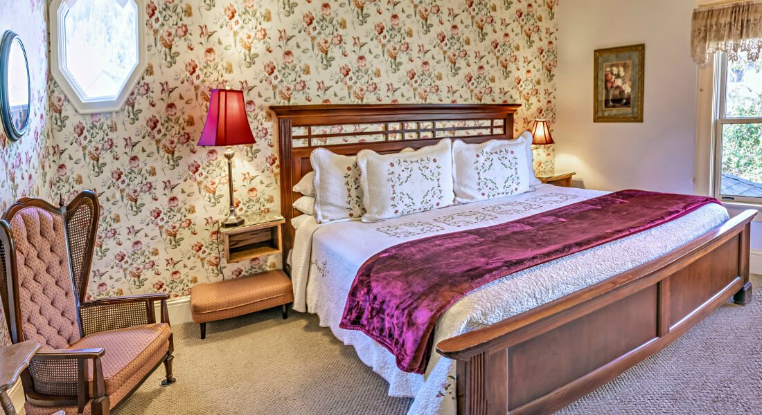 A guest bedroom with floral wallpaper, carpeted floors, white bedding and two nightstands with reading lamps