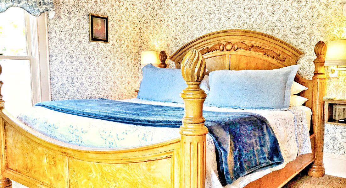 Guest bedroom with patterned wallpaper, white and blue print bedding, a wooden bedframe and two reading lights