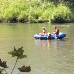 River Raft on the Rogue River with two people and a dog