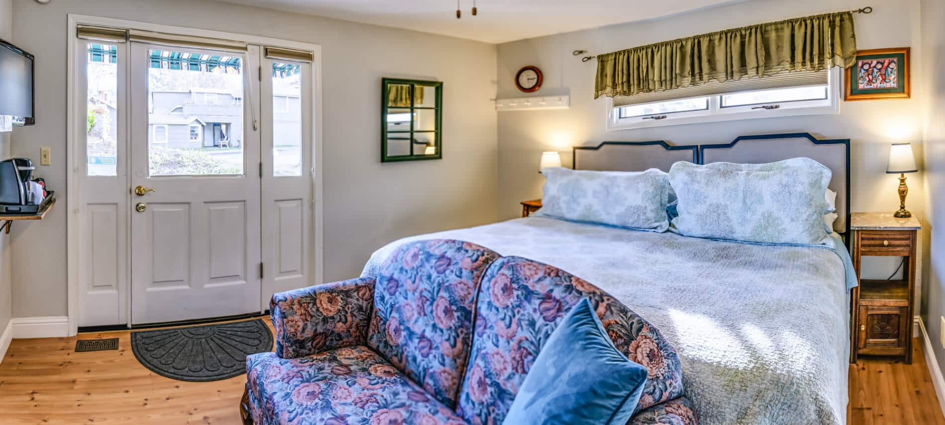 A white guest room with light blue and white patterned bedding and a blue and pink floral couch