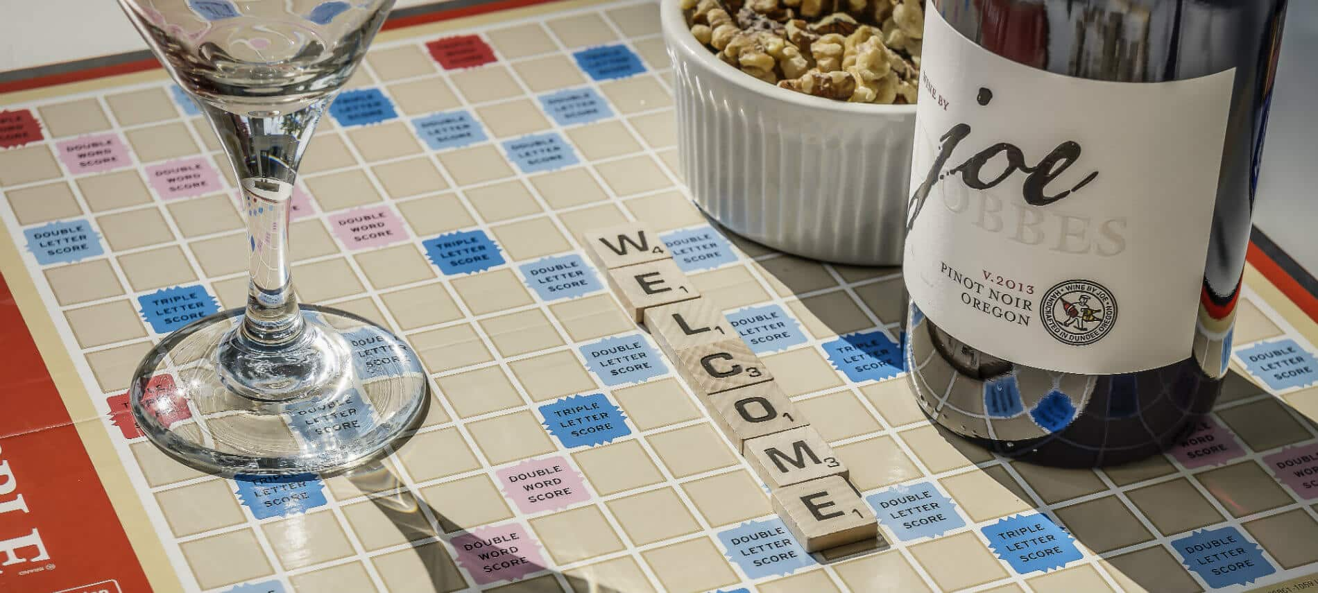 A crystal wine glass and a bottle of wine sit on a scrabble board with the word welcome spelled out