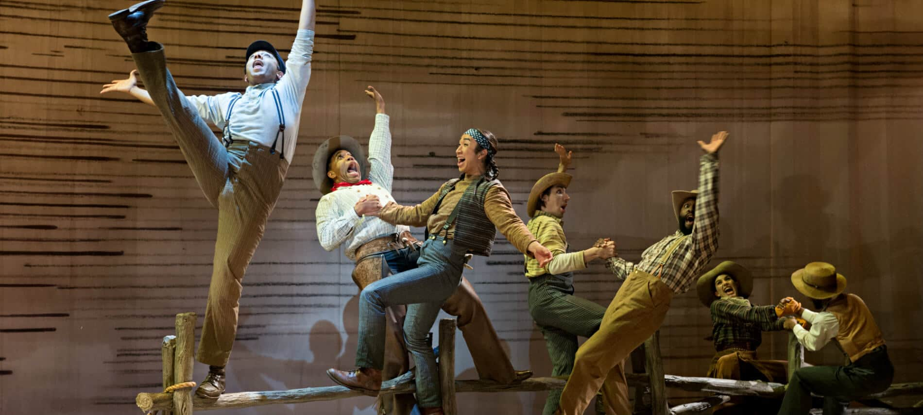 Several cast members in western themed costumes standing in dancing positions on a brown stage