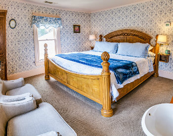 Carpeted guest room with blue and white print wallpaper, blue and white bedding, and two cushioned sitting chairs