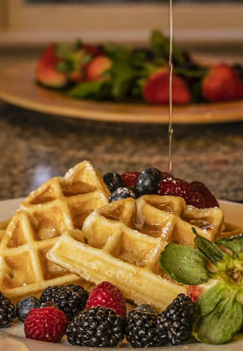 A plate of sliced golden waffles surrounded by blackberries ,raspberries and blueberries, all drizzled in syrup