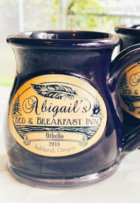 A navy ceramic mug with a cream label which says Abigail's Bed & Breakfast Inn, Othello, 2018, Ashland, Oregon