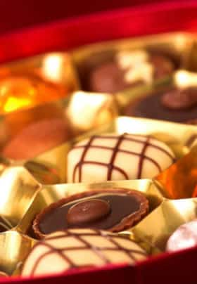 Several white and deep brown boxed chocolates in golden packaging and a shiny red container
