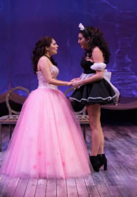 A woman in a pink gown standing on a stage with a woman in a black and white maid outfit